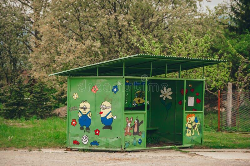 有街道画的公交车站在小村庄 库存照片