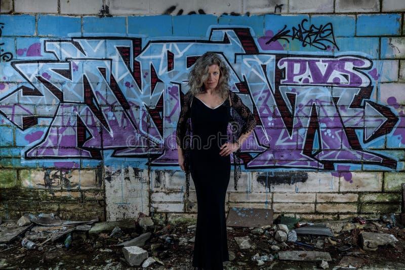 有街道画墙壁的典雅的夫人在遗弃大厦 免版税库存照片