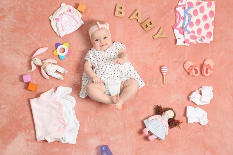 有衣物和辅助部件的逗人喜爱的矮小的婴孩 库存图片