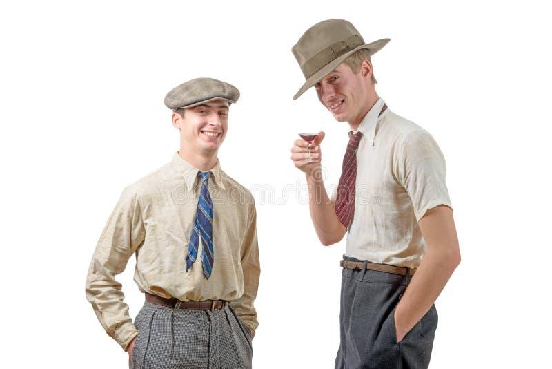 有衣裳和盖帽的两个年轻人在20s样式 免版税库存图片