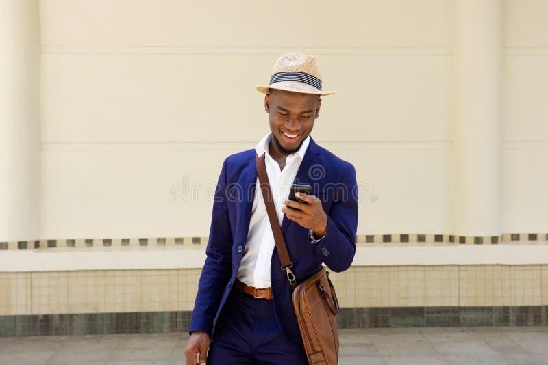 有袋子和手机的愉快的年轻非洲人 免版税库存图片