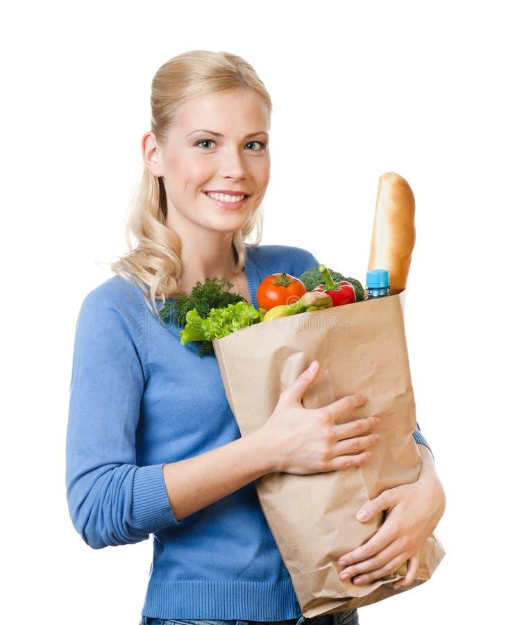 有袋子的俏丽的妇女有很多健康吃 免版税库存图片