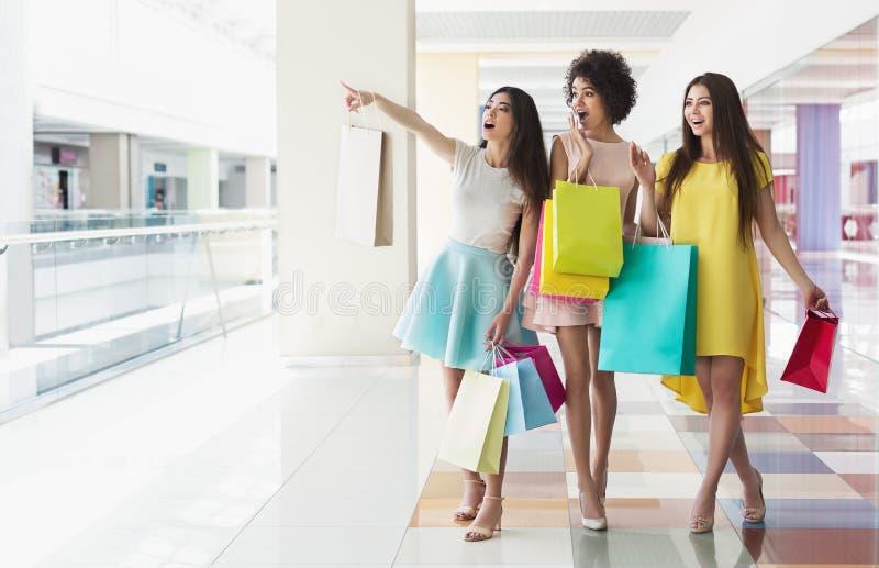 有袋子的多种族女朋友一起购物在购物中心的 库存图片