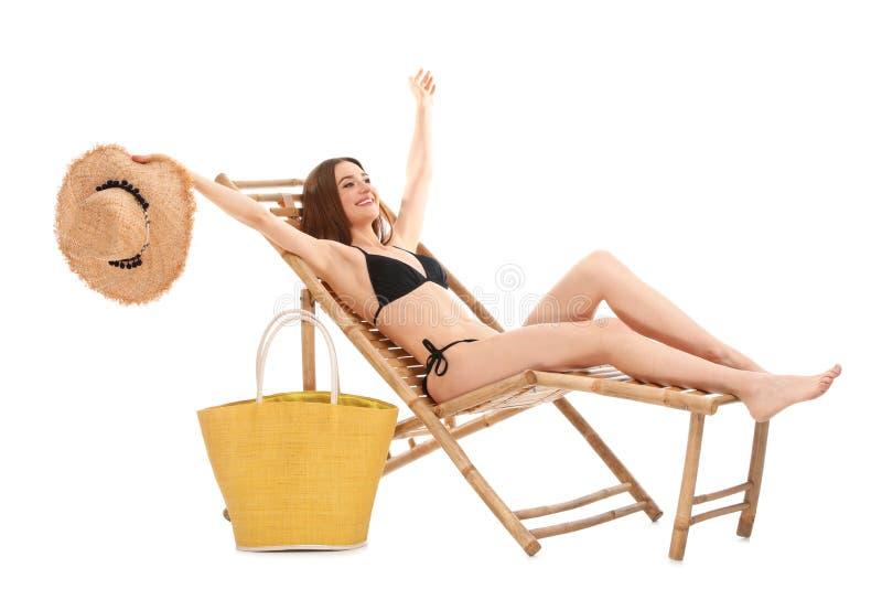 有袋子的年轻女人在反对白色背景的太阳懒人 ?? 图库摄影