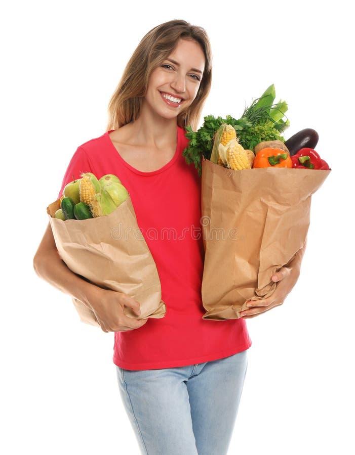 有袋子的年轻女人在白色的新鲜蔬菜 免版税图库摄影