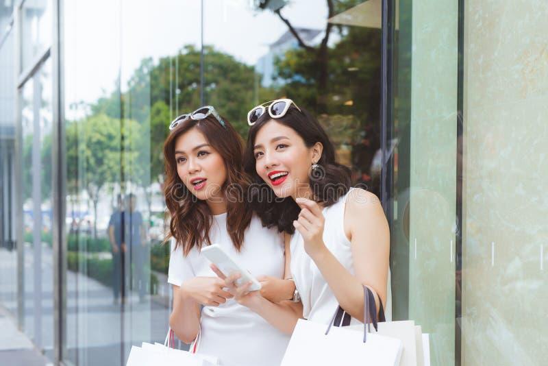 有袋子的年轻美丽的愉快的妇女购物与在街道的一智能手机的 库存图片