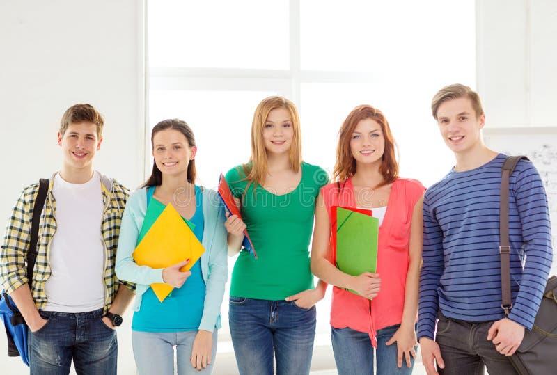 有袋子的微笑的学生和文件夹在学校 库存图片