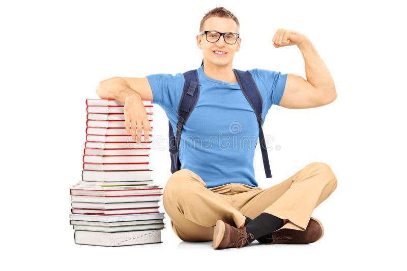 有袋子的微笑的男学生在显示他的二头肌的书附近 库存照片