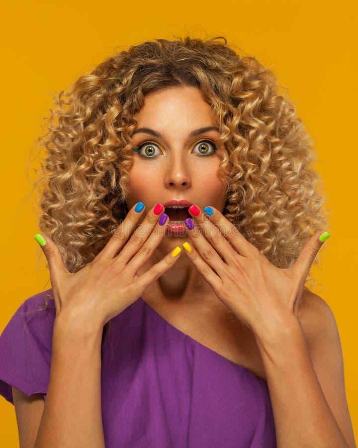 有袋子的微笑的美丽的年轻女人 有非洲的发型和括号的