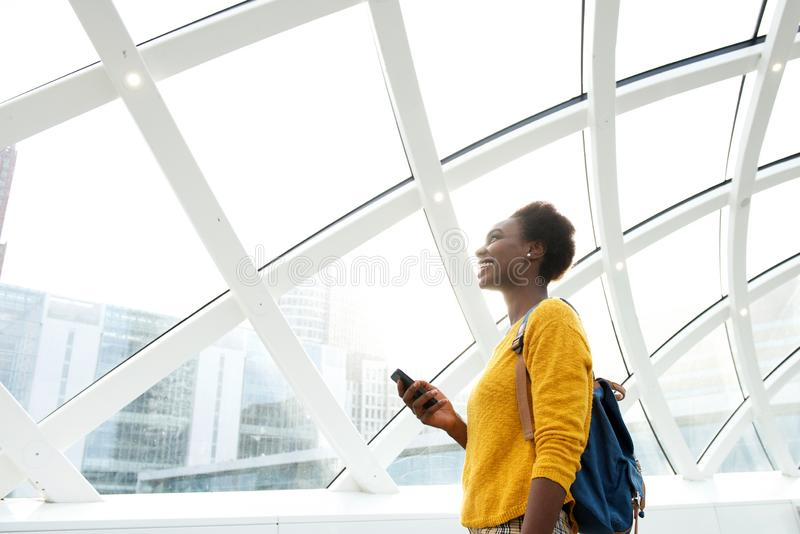 有袋子的微笑的非裔美国人的妇女和在驻地的手机 库存图片
