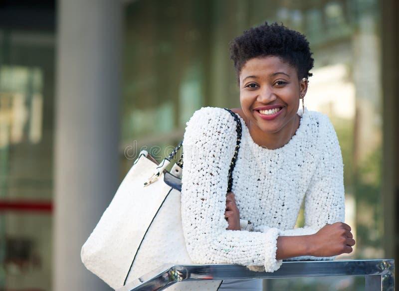 有袋子的微笑的非裔美国人的妇女 免版税图库摄影