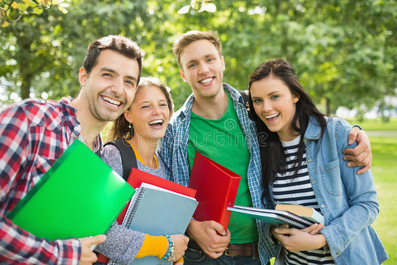有袋子的快乐的大学生和书在公园 免版税库存照片