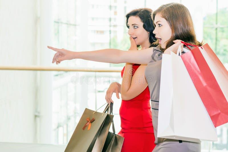 有袋子的愉快的时尚妇女室内在购物中心 免版税图库摄影