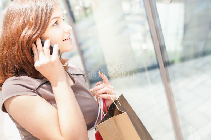 有袋子的愉快的美丽的妇女使用手机,购物中心 免版税库存图片