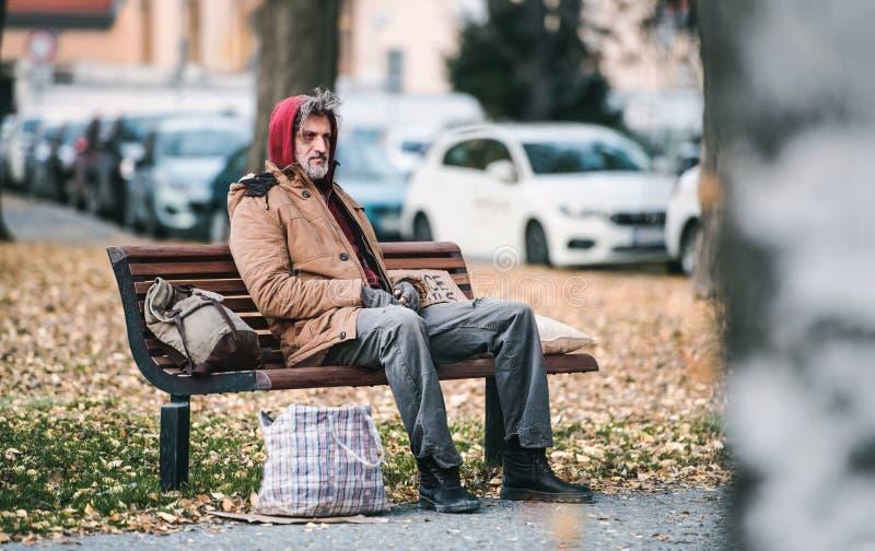 有袋子的无家可归的叫化子人坐长凳户外在城市 复制空间 免版税库存照片