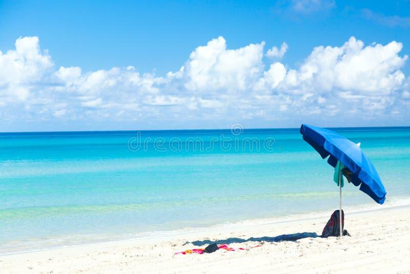 有袋子的蓝色在海洋海滩的伞和毛巾与美丽的天空蔚蓝和云彩 放松,假期田园诗背景 免版税库存图片