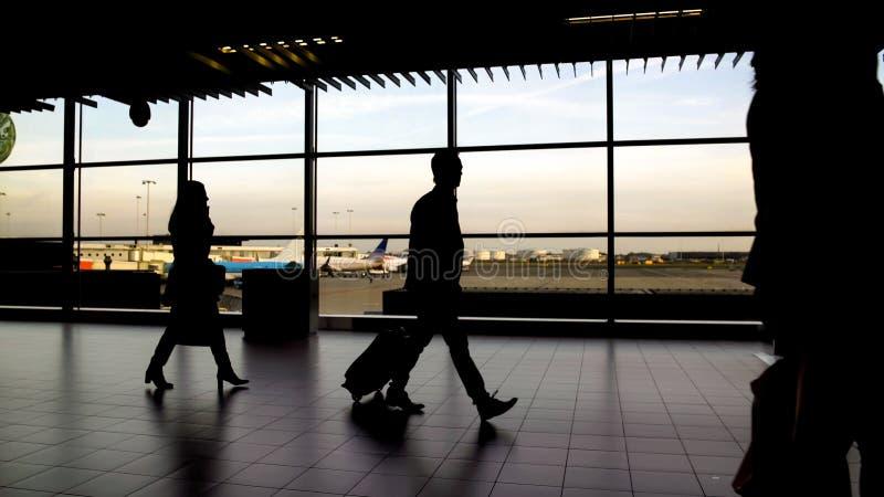 有袋子的走在机场终端,旅行和假期的男人和妇女 库存图片