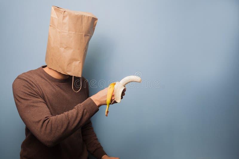 有袋子的年轻人在他的使用香蕉的头作为枪 免版税库存图片