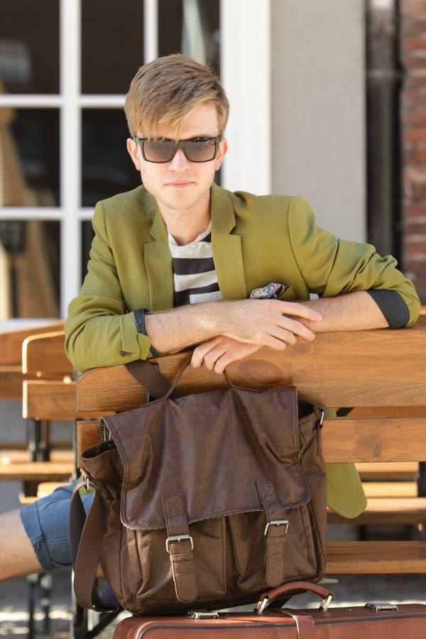 有袋子的年轻英俊的人在长凳等待 免版税库存照片