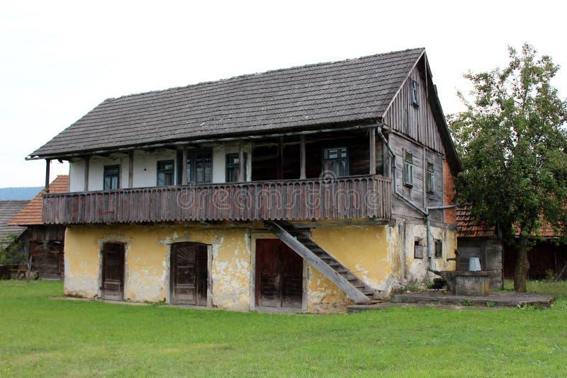 有被上升的前沿的大老木家庭房子和在具体井旁边的被毁坏的委员会与生锈的水泵 图库摄影