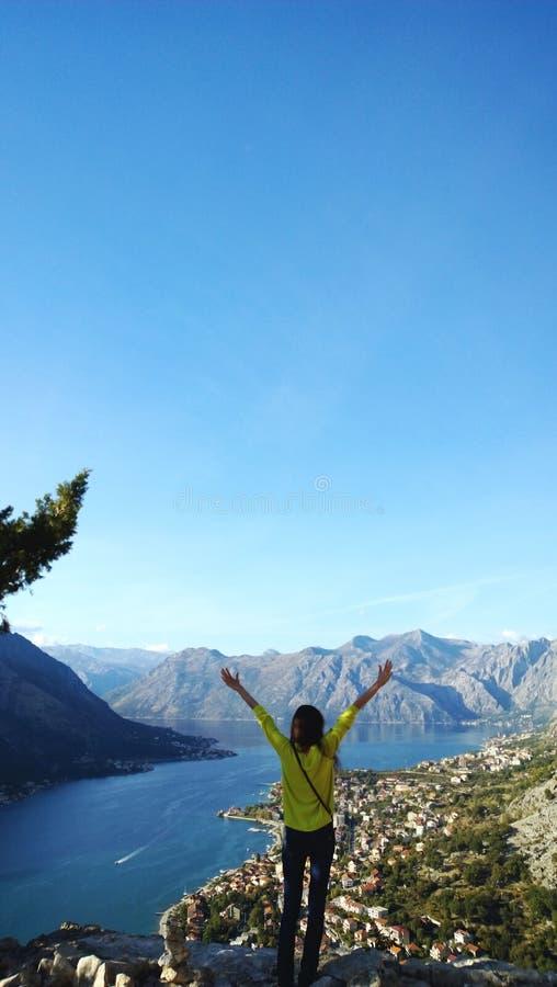 有被上升的胳膊愉快的旅途的女孩 敬佩博卡队海湾在黑山 垂直的视图 图库摄影