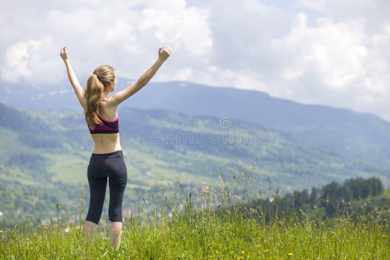 有被举的胳膊的亭亭玉立的年轻女人户外在美好的山风景背景在晴朗的夏日 免版税图库摄影