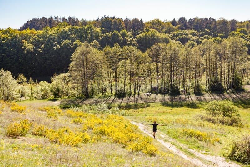 有被举的胳膊的人走在夏天绿色草甸的围拢了b 免版税库存图片