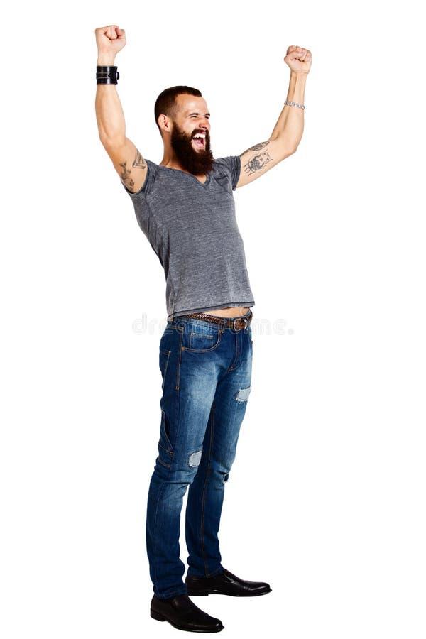 有被举的胳膊的激动的英俊的被刺字的有胡子的人 库存图片