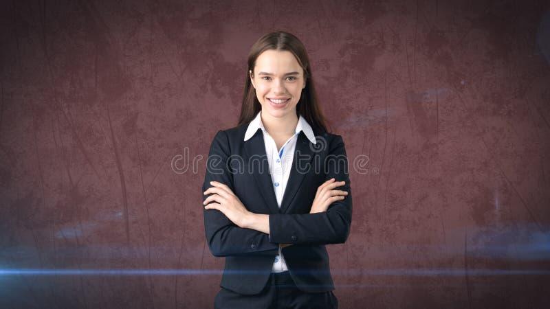有被交叉的双臂的微笑的女实业家 站立在红色背景 库存照片
