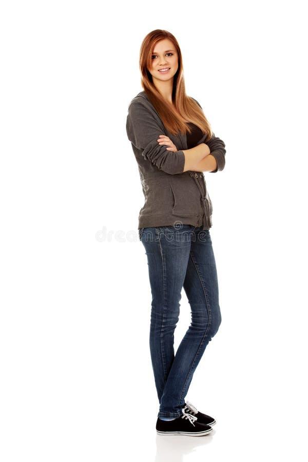 有被交叉的双臂的愉快的青少年的妇女 免版税库存图片
