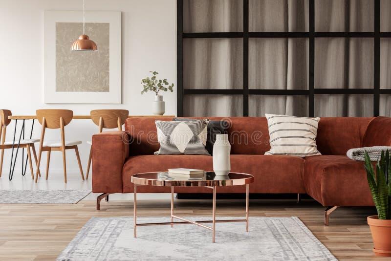 有被仿造的枕头的时髦的棕色壁角沙发在与直棂墙壁的典雅的客厅内部 库存图片