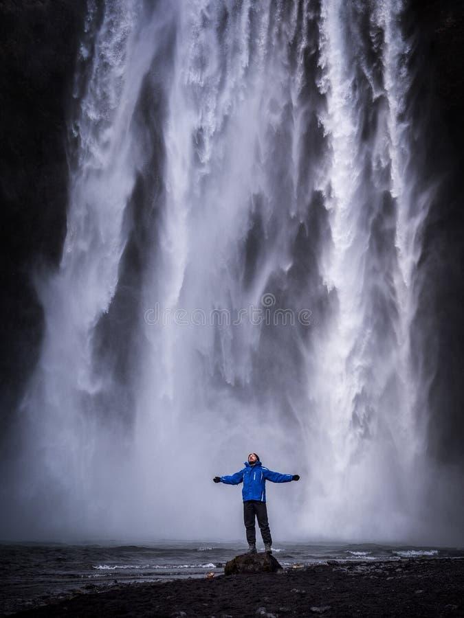 有被伸出的胳膊的旅客在瀑布附近在冰岛 免版税图库摄影