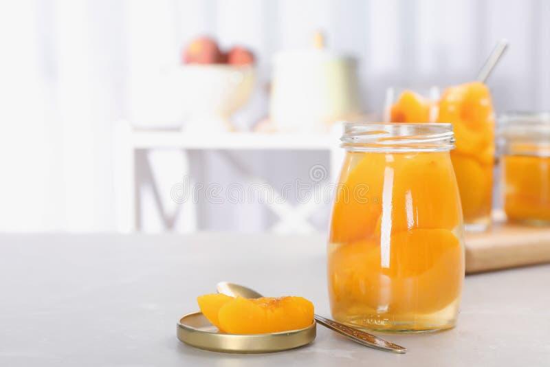 有被保存的桃子一半的玻璃瓶子在桌上 库存照片