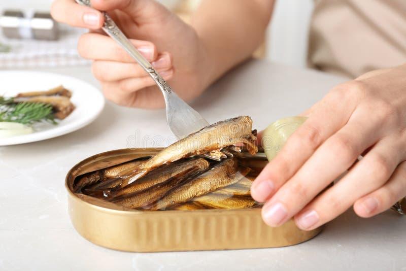 有被保存的鱼锡罐的妇女  库存图片