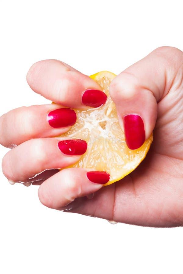 有被修剪的钉子的手紧压在白色的柠檬 免版税库存图片