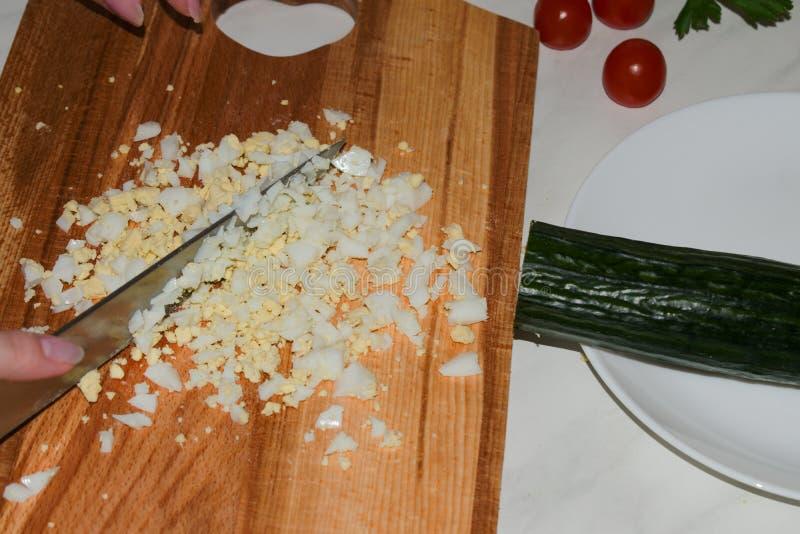 有被切的刀子的美好的女性手煮沸了鸡蛋 库存图片