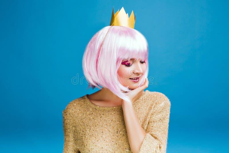 有被剪的桃红色头发的时髦的迷人的年轻女人在蓝色背景 金黄毛线衣,在头的冠,微笑与关闭 免版税库存照片