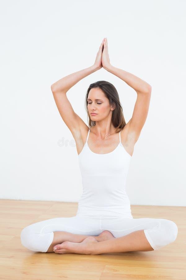 有被加入的手天花板的妇女在健身演播室 库存图片
