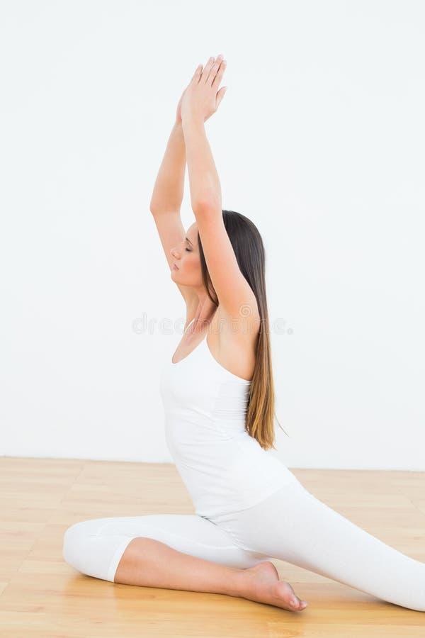 有被加入的手天花板的被定调子的妇女在健身演播室 免版税库存照片