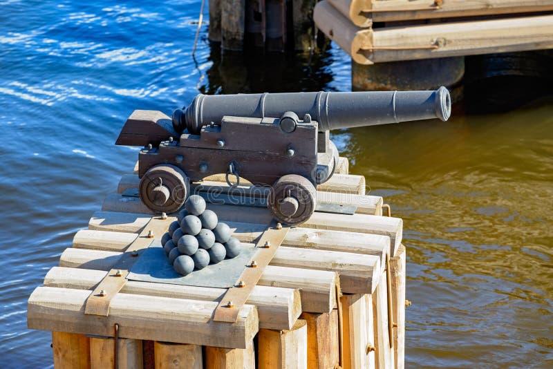 有被堆积的古炮炮弹的古老大炮 免版税库存照片