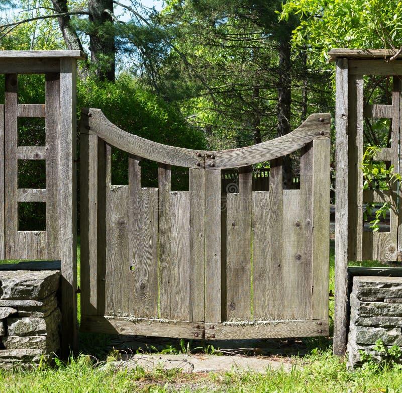 有被堆积的石头、草和树的困厄的木门 库存图片