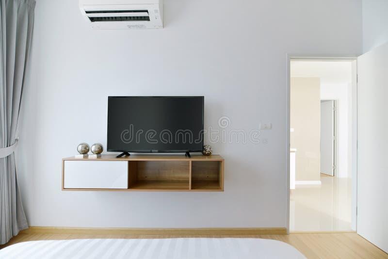 有被带领的电视的现代空的卧室在白色墙壁和木架子上 库存图片