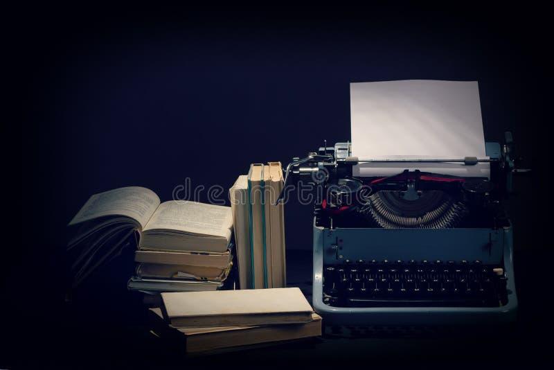 有被开张的书减速火箭的颜色的老打字机在服务台上 图库摄影