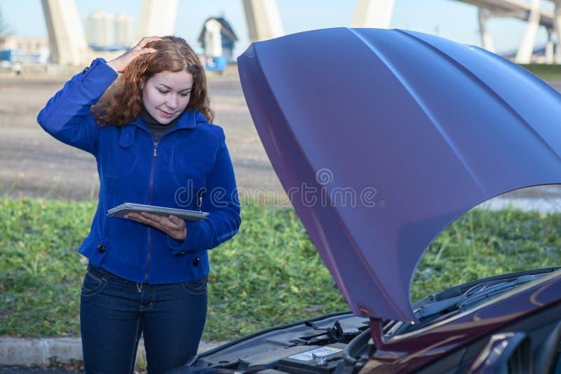 有被开张的汽车敞篷和片剂个人计算机的认为的妇女 库存照片