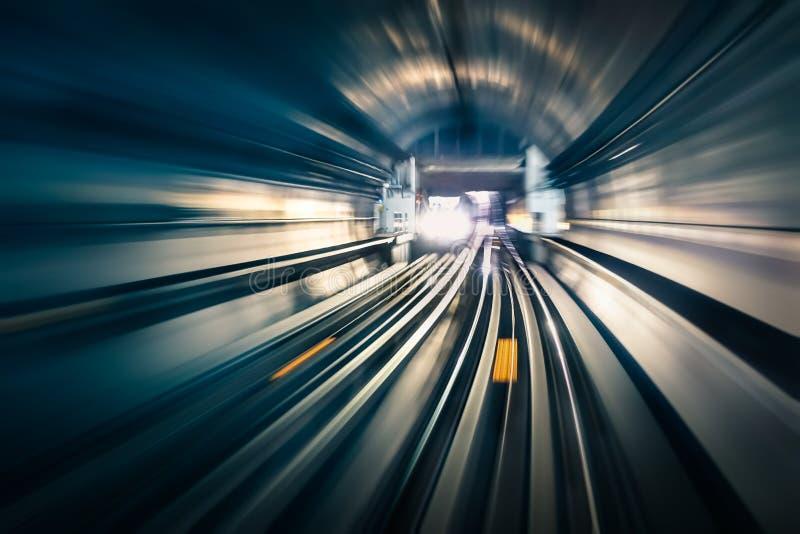 有被弄脏的轻的轨道的地铁隧道与到达的火车 免版税库存照片