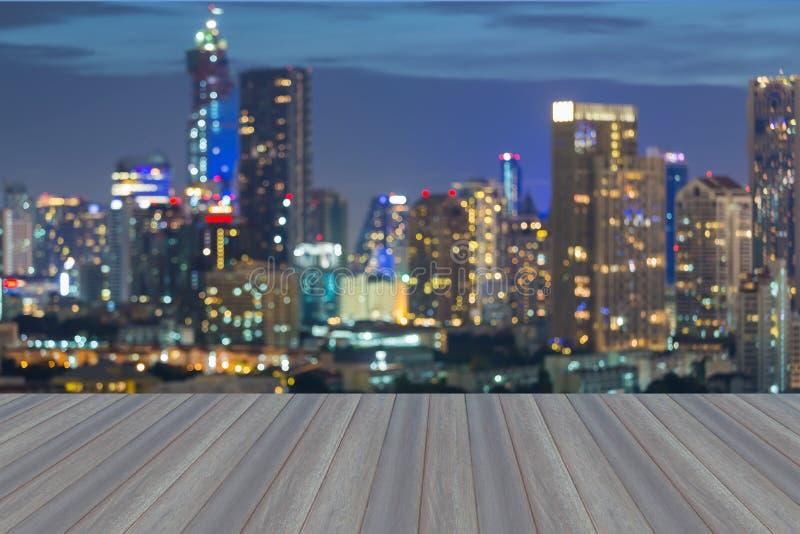 有被弄脏的bokeh城市光的木平台在微明期间 免版税库存照片