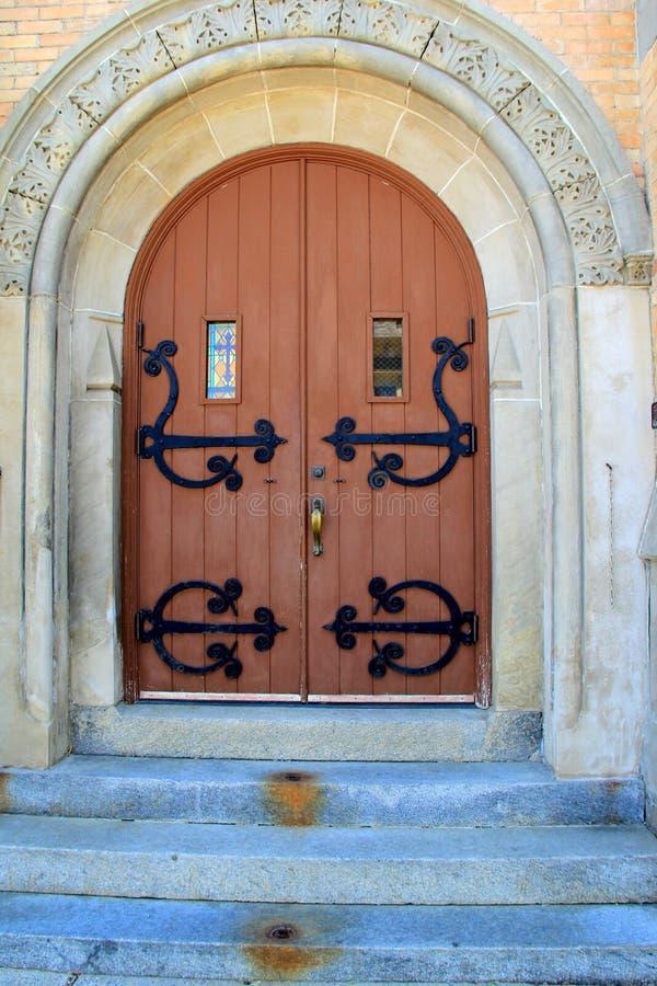 有被成拱形的门道入口和华丽入口的老石教会 免版税库存照片
