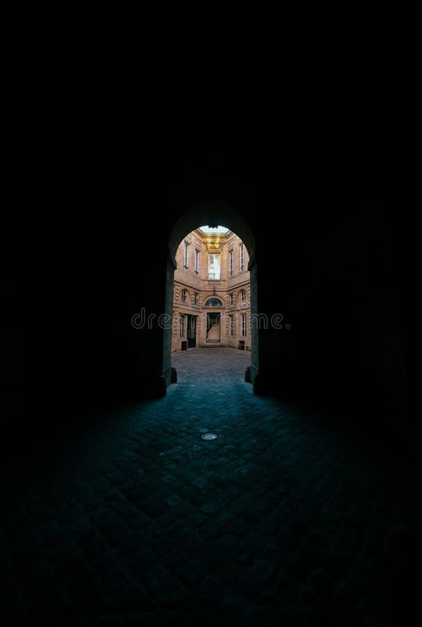 有被成拱形的门道入口的黑暗的走廊以一个混凝土建筑为目的 免版税库存图片
