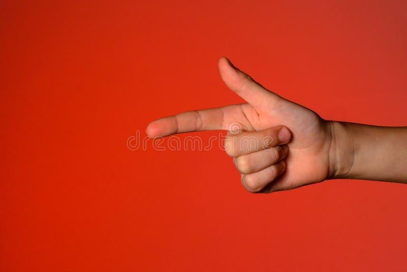 有被折叠的手指的人的手,显示象征手枪的一个食指,隔绝在红色背景 免版税库存照片