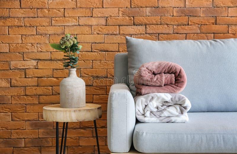 有被折叠的温暖的格子花呢披肩的沙发在客厅内部  免版税库存图片